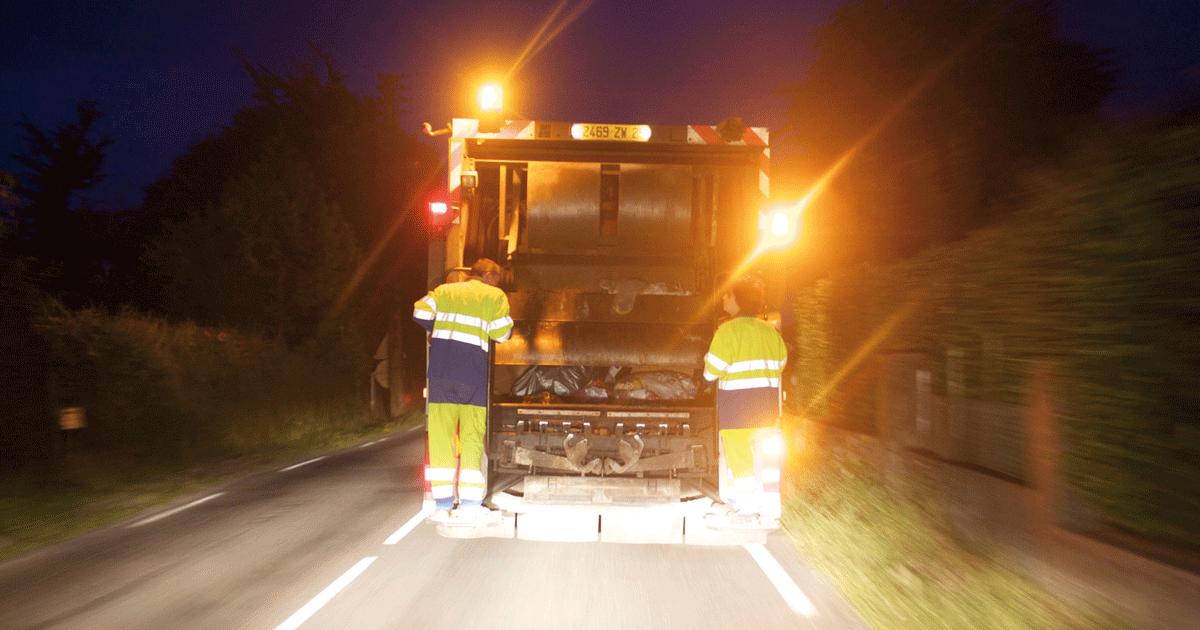 Deux agents de collecte des déchets à l'arrière d'un camion en train de rouler