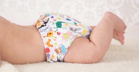 bébé allongé sur le ventre portant une couche lavable